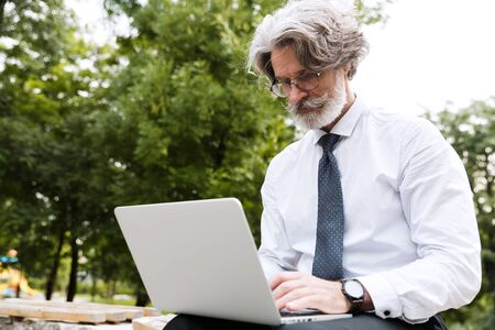 Photo of elderly thinking businessman in eyeglasses using laptop while sitting on bench in summer park