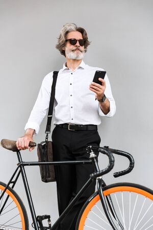 Photo of thinking old businessman in sunglasses using cellphone while standing with bicycle over gray wall outdoors