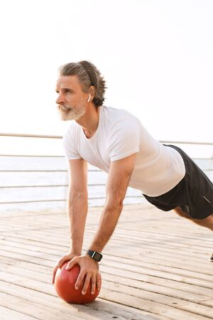 Image of bearded old man in sportswear using earpod while doing exercise with medicine ball near seaside in morning Stock Photo