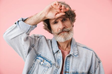 Portrait of disappointed old man with gray beard looking at camera and touching his head isolated over pink background