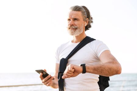 Image of satisfied elderly man in sportswear using smartwatch and cellphone while working out at promenade in morning