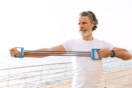 Bild eines starken reifen Mannes in Sportkleidung mit Ohrstöpsel, während er morgens mit Expander in der Nähe der Küste trainiert Standard-Bild