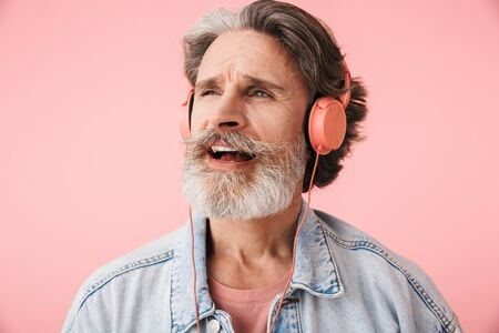 Portrait closeup of cheerful old man 70s with gray beard singing while listening to music with headphones isolated over pink background