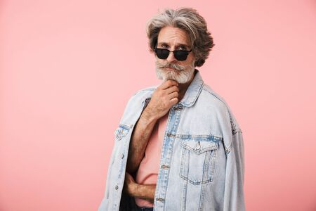 Portrait of mature old man with gray beard wearing sunglasses and denim jacket looking at camera isolated over pink background Reklamní fotografie