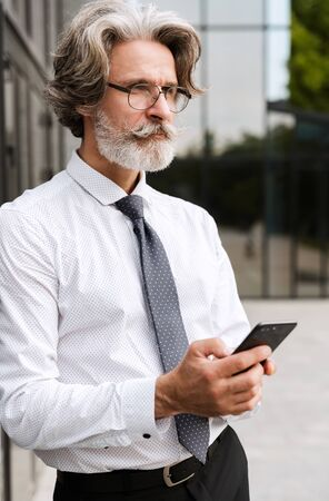 Photo of serous mature businessman in eyeglasses typing on cellphone while leaning on wall outdoors