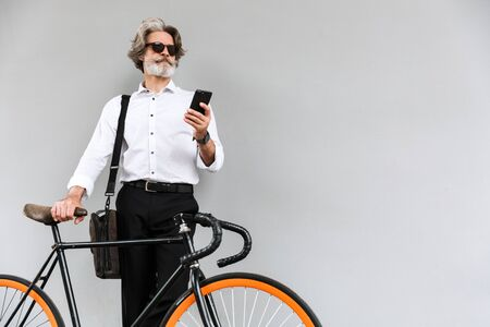 Photo of caucasian old businessman in sunglasses using cellphone while standing with bicycle over gray wall outdoors