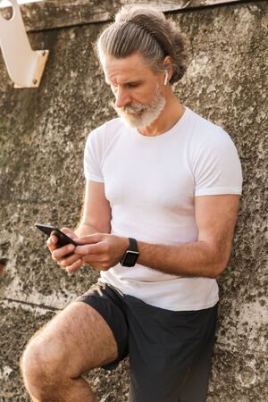 Image of caucasian elderly man in sportswear using earpod and cellphone while leaning on concrete wall in morning outdoors