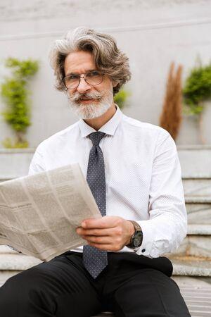 Photo of smiling elderly businessman in eyeglasses reading newspaper while sitting outdoors 写真素材