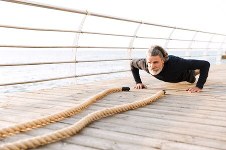 Image of gray-haired mature man in tracksuit doing exercise with battle ropes while working out near seaside in morning