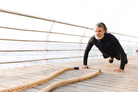 Image of caucasian mature man in tracksuit doing exercise with battle ropes while working out near seaside in morning