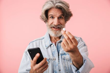 Portrait closeup of satisfied old man 70s with gray beard holding smartphone while listening to music with earphones isolated over pink background Reklamní fotografie
