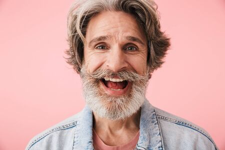Portrait closeup of cheerful old man 70s with gray beard smiling and looking at camera isolated over pink background