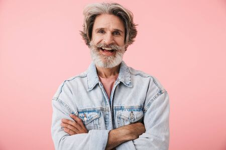 Portrait of handsome old man with gray beard laughing and holding hands crossed isolated over pink background Reklamní fotografie