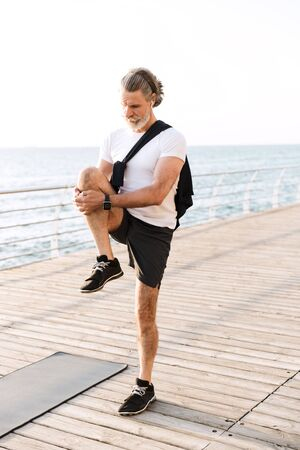 Image of concentrated old man in sportswear using earpod while stretching his leg at boardwalk in morning Stok Fotoğraf