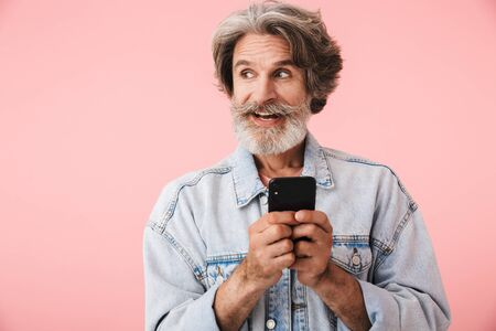 Portrait of a cheerful middle aged man wearing casual outfit standing isolated over pink background, using mobile phone
