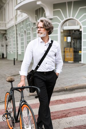 Photo of brooding mature businessman in eyeglasses walking with bicycle on city street Reklamní fotografie