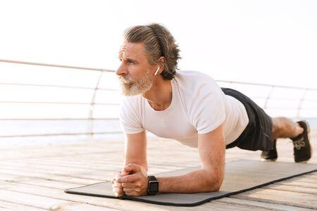 Image of bearded mature man in sportswear using earpod while doing exercise near seaside in morning 写真素材