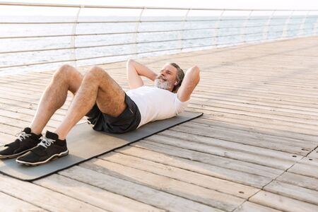 Image of calm old man in sportswear using earpod while doing exercise on mat at boardwalk in morning