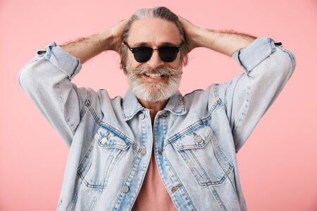 Portrait of a cheerful middle aged man wearing casual outfit standing isolated over pink background, posing in sunglasses Reklamní fotografie