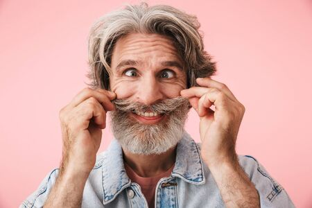 Portrait of cheerful old man with gray beard grimacing and having fun at camera isolated over pink background 写真素材
