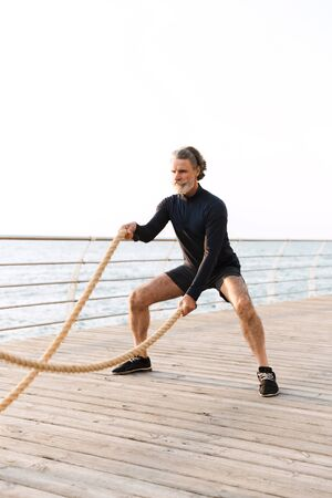 Image of focused mature man in tracksuit doing exercise with battle ropes while working out near seaside in morning