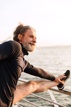 Imagen de un anciano complacido en chándal estirando las piernas sobre la barandilla mientras hace ejercicio cerca de la playa en la mañana