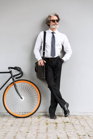 Photo of serious old businessman in sunglasses looking aside while standing with bicycle over gray wall outdoors