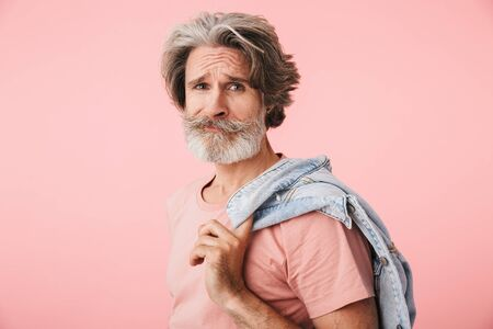 Portrait of displeased mature man 70s with gray beard smiling and holding his denim jacket over his shoulder isolated over pink background