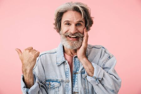 Portrait of joyful old man with gray beard laughing and pointing finger at copyspace isolated over pink background