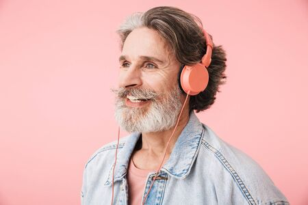 Portrait closeup of joyful old man 70s with gray beard singing while listening to music with headphones isolated over pink background Reklamní fotografie