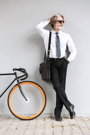 Photo of respectable old businessman in sunglasses looking aside while standing with bicycle over gray wall outdoors Reklamní fotografie
