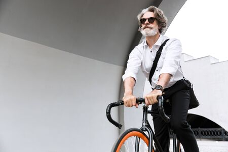 Photo of confident mature businessman in sunglasses and white shirt riding bicycle on city street Reklamní fotografie