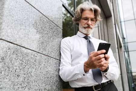 Photo of concentrated elderly businessman in eyeglasses typing on cellphone while leaning on wall outdoors