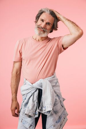 Portrait closeup of pleased mature man 70s with gray beard smiling and looking at camera isolated over pink background