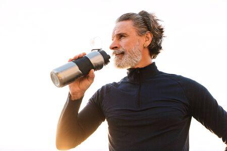Bild eines athletischen älteren Mannes im Trainingsanzug, der Wasser aus der Flasche trinkt, während er morgens im Freien trainiert