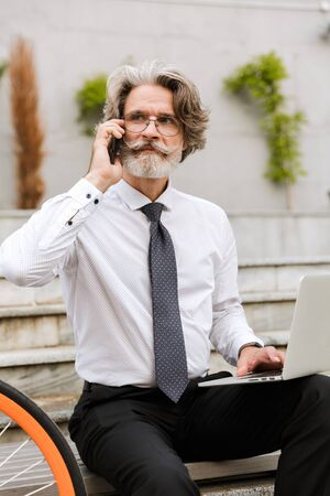 Photo of mature confident businessman in eyeglasses using cellphone and laptop while sitting on bench with bicycle outdoors