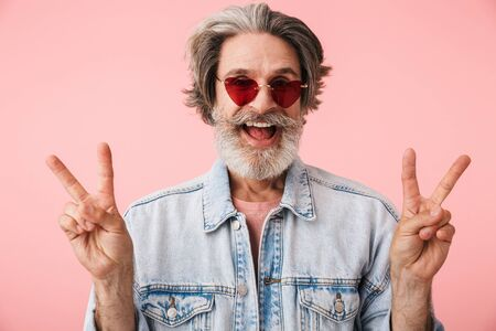 Portrait of happy old man with gray beard wearing fashion sunglasses smiling and showing peace fingers isolated over pink background