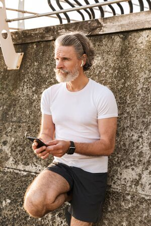 Image of gray-haired elderly man in sportswear using earpod and cellphone while leaning on concrete wall in morning outside
