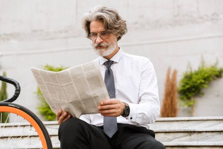 Photo of serious elderly businessman in eyeglasses reading newspaper while sitting with bicycle outdoors 写真素材