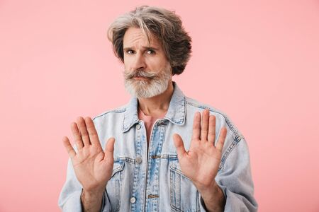 Portrait of a middle aged man wearing casual outfit standing isolated over pink background, showing disbelief
