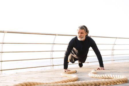 Image of sporty elderly man in tracksuit doing exercise with battle ropes while working out near seaside in morning