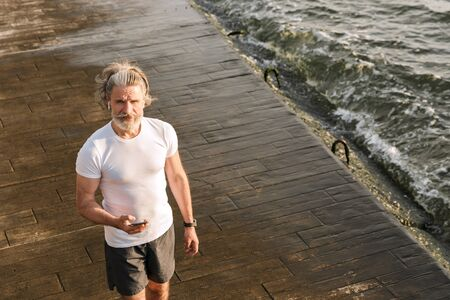 Image of bearded mature man in sportswear using earpod and cellphone while walking near seaside in morning