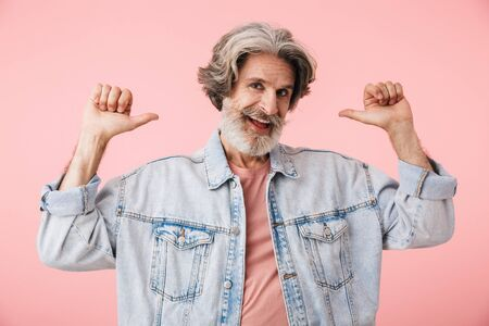 Portrait of cheerful old man with gray beard pointing fingers backward at copyspace isolated over pink background Stok Fotoğraf