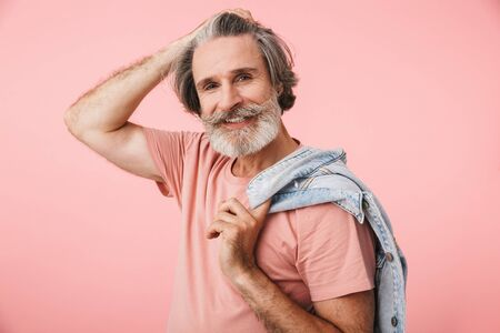 Portrait of masculine old man with gray beard smiling at camera and holding denim jacket isolated over pink background 写真素材