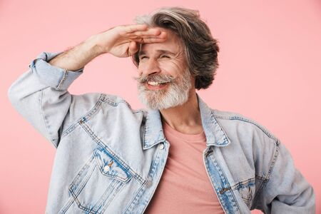 Portrait of pleased old man with gray beard laughing and looking aside at copyspace with hand at forehead isolated over pink background