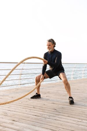Image of sporty mature man in tracksuit doing exercise with battle ropes while working out near seaside in morning