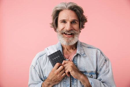Portrait closeup of joyful old man 70s with gray beard smiling while holding passport and travel ticket isolated over pink background Archivio Fotografico - 131960401