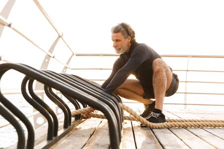 Image of bearded old man in tracksuit doing exercise with battle ropes while working out near seaside in morning