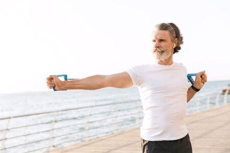 Imagen de atlético anciano en ropa deportiva usando earpod mientras hace ejercicio con expansor cerca de la playa en la mañana