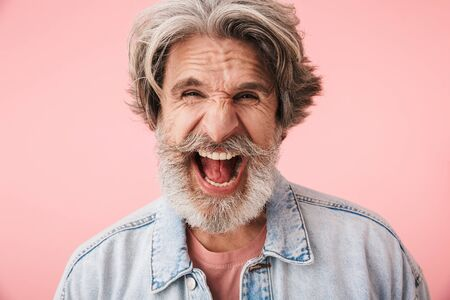 Portrait of emotional old man with gray beard expressing anxiety and screaming at camera isolated over pink background